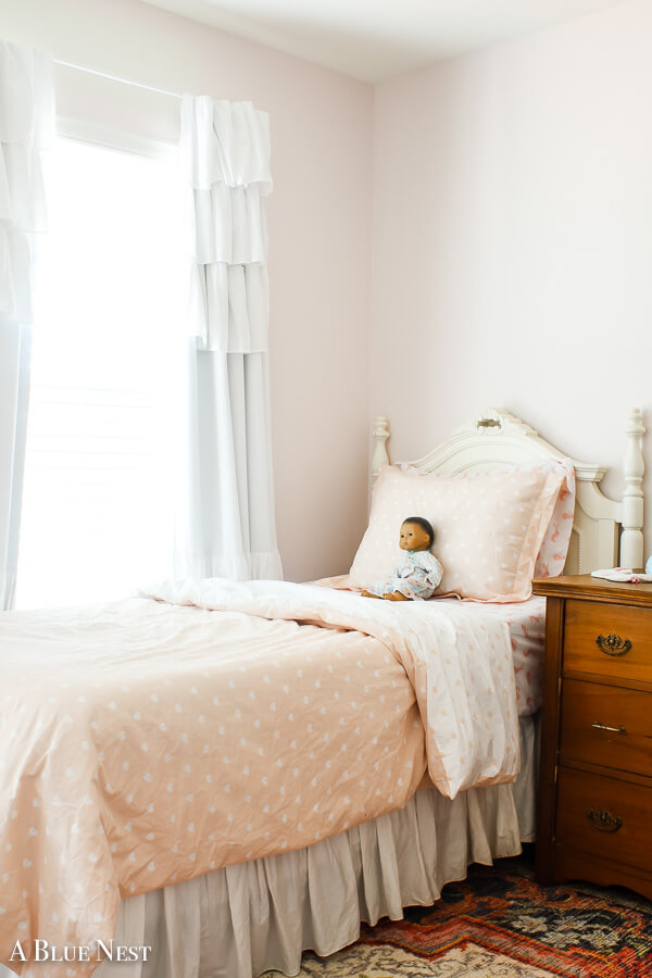 girl's twin bed with Benjamin Moore First Light on the walls