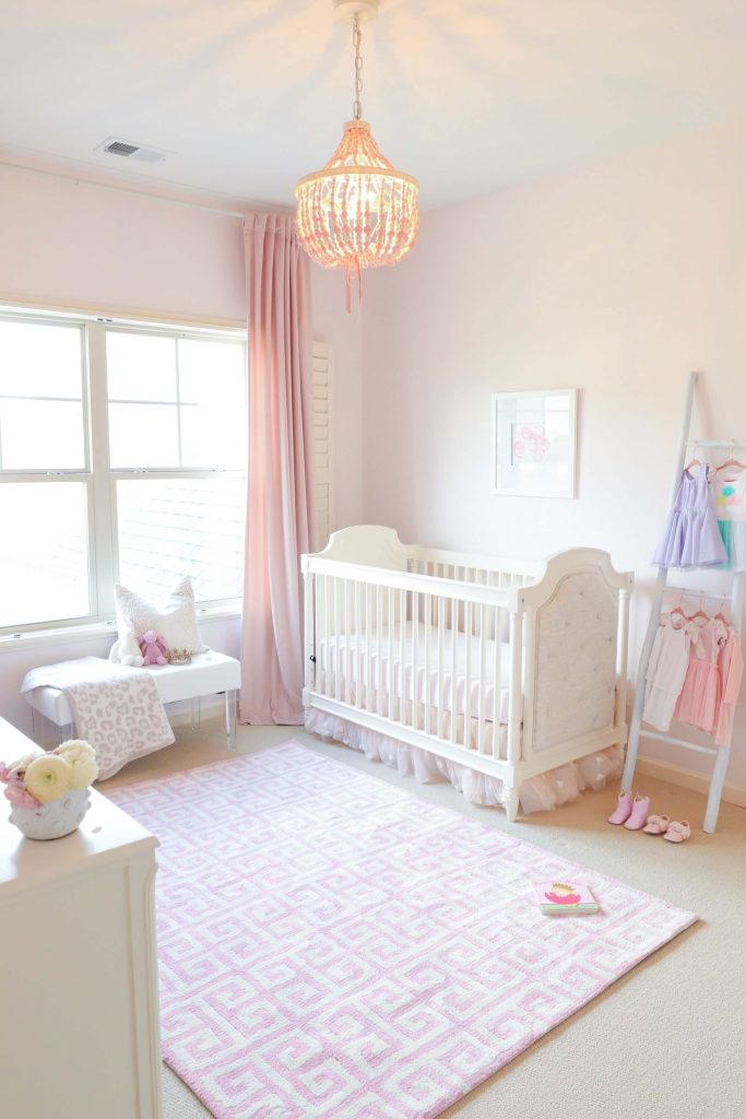 girls nursery with white crib and Benjamin Moore Pink Bliss on the walls
