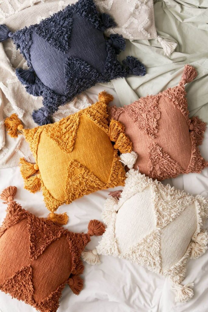 5 pillows with tassles laying on white comfortor