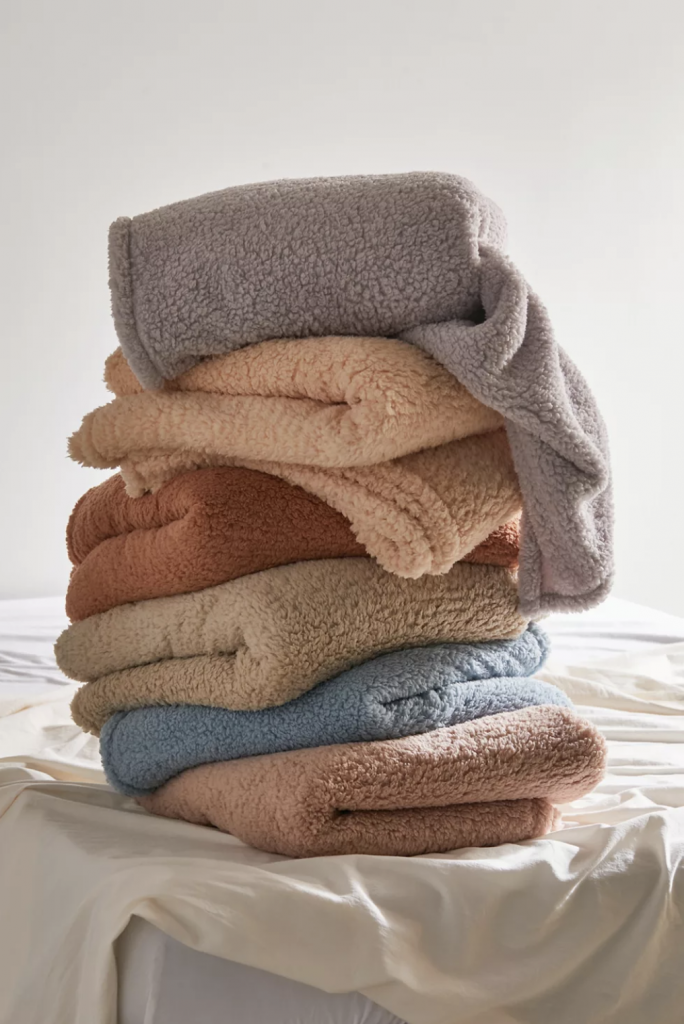 stack of fuzzy blankets in muted colors