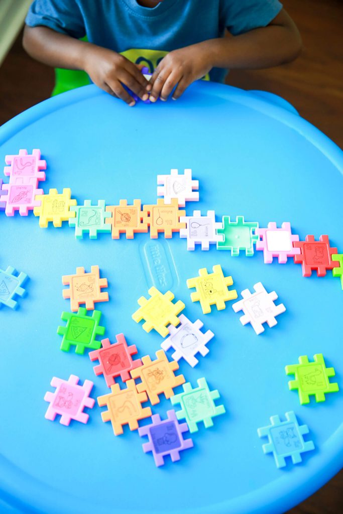 bright blue table with little boy putting together puzzle pieces