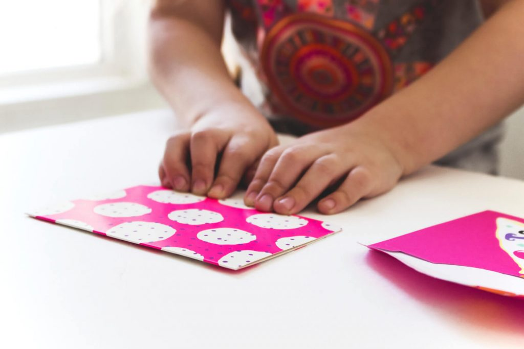 little kids hands holding a pink and white card