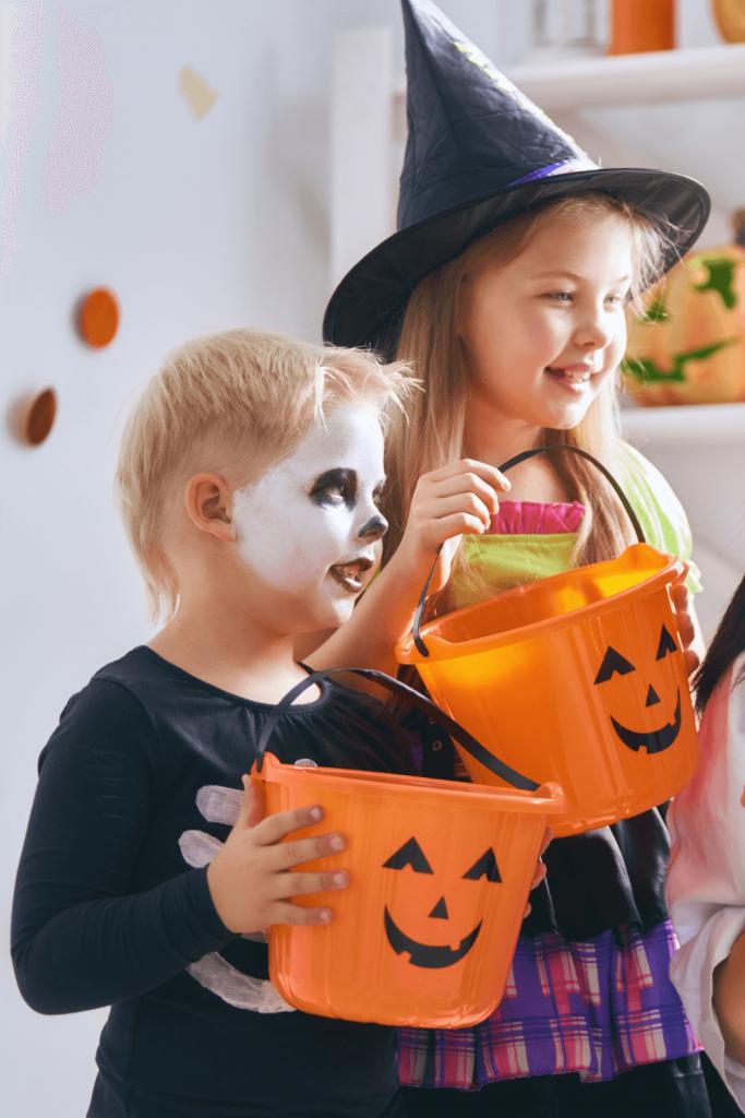 2 kids holding jack o lantern candy baskets dressed up for Halloween