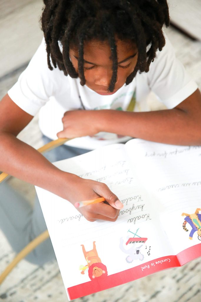 black girl with twists writing in a homework book