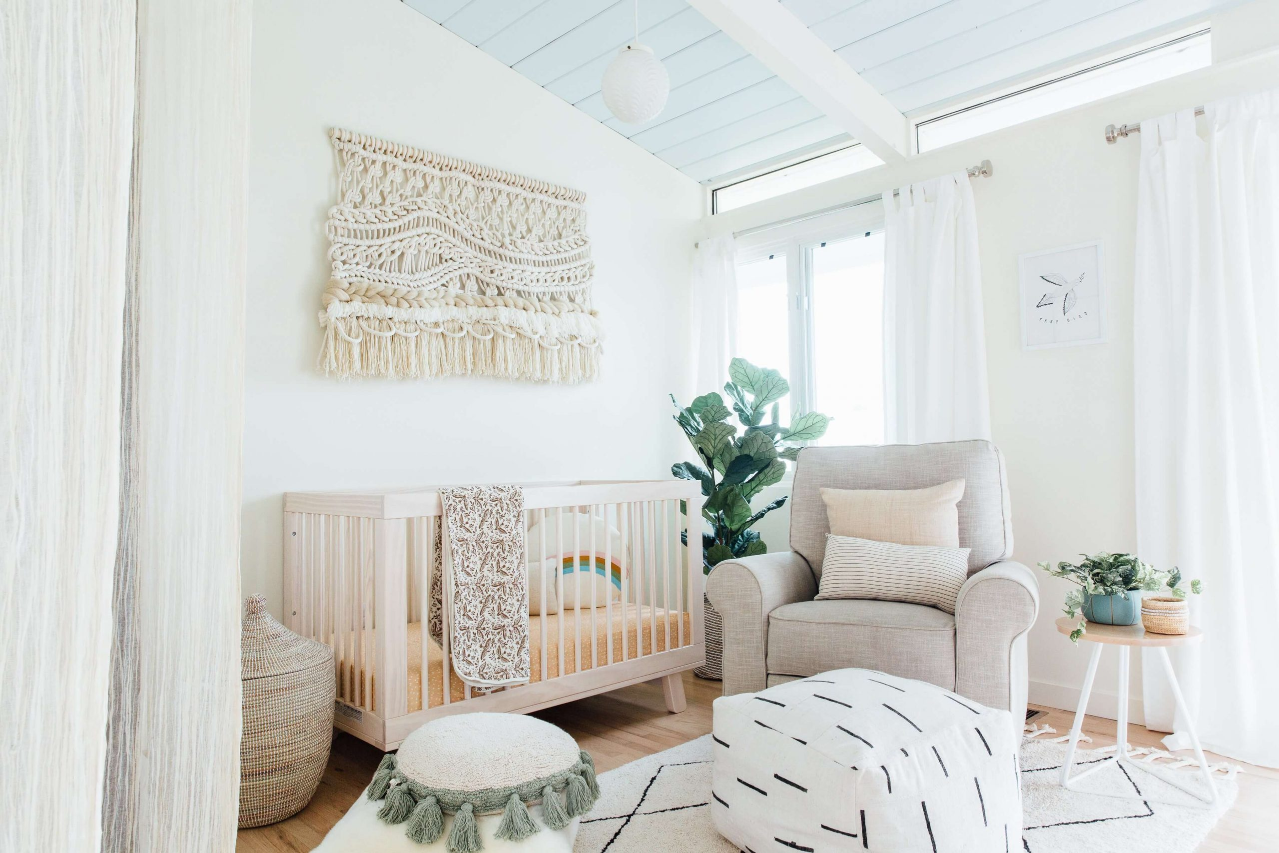 neutral nursery design with fringe wall hanging over crib