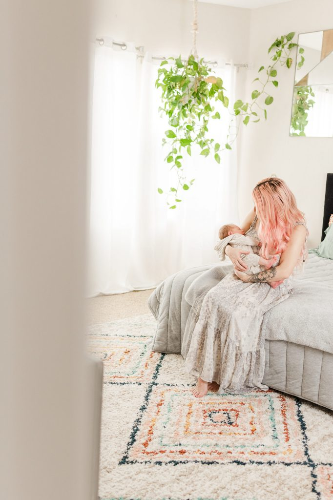 blonde mom holding baby on the end of the bed with fern hanging over her