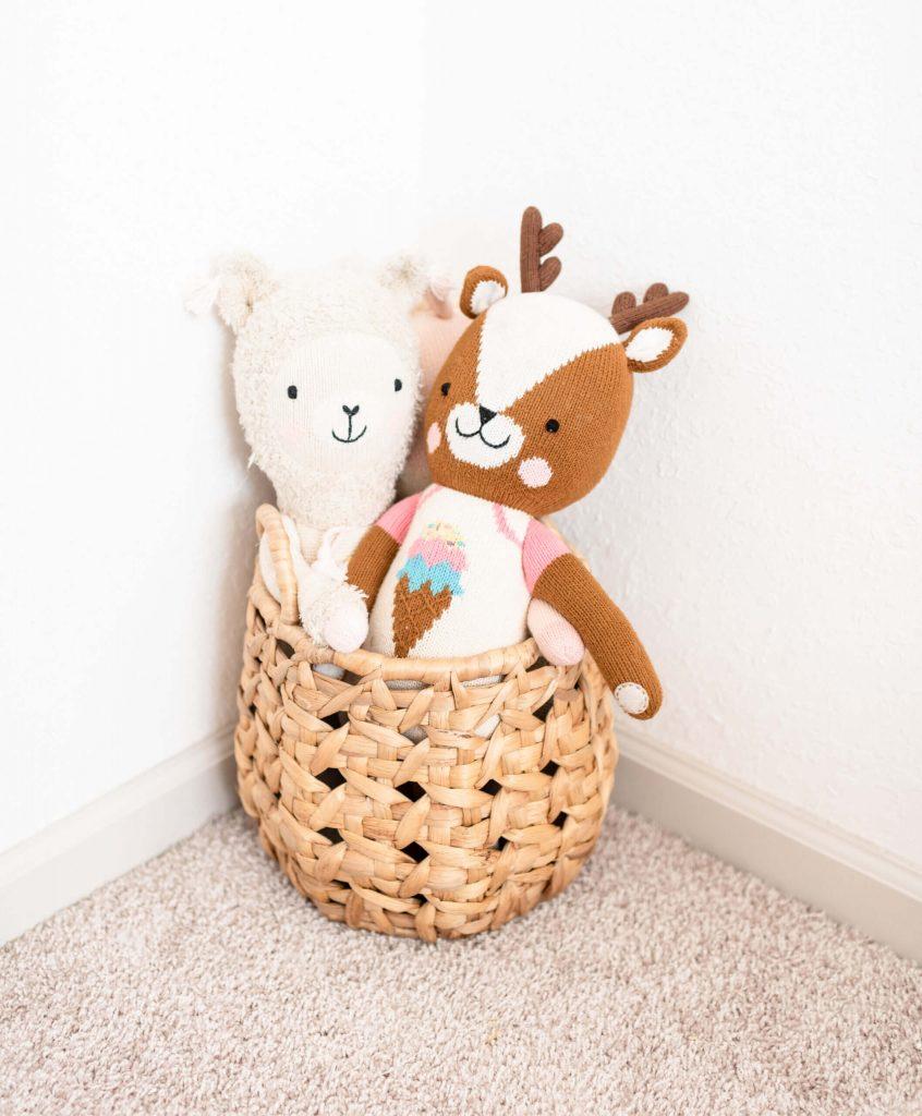2 stuffed dolls in a wicker basket