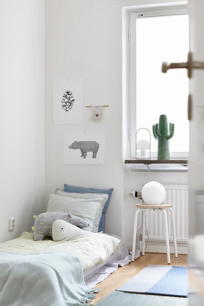 neutral modern minimalist children's room with bed on the floor and whimsical animal wall art