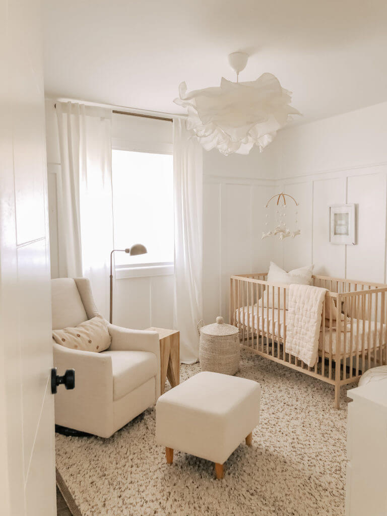 neutral minimalist nursery with wood crib and white walls and white furniture