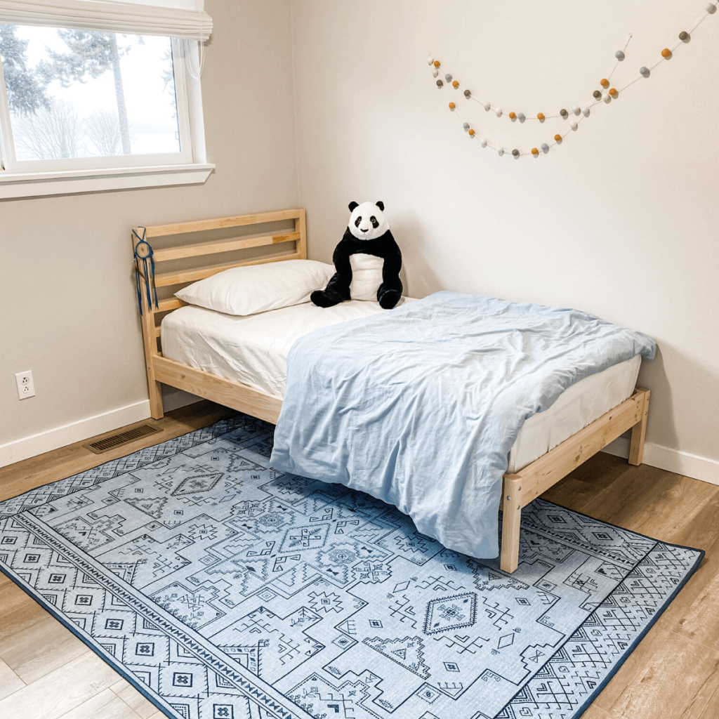 modern minimalist children's bedroom with blue rug and wood bed