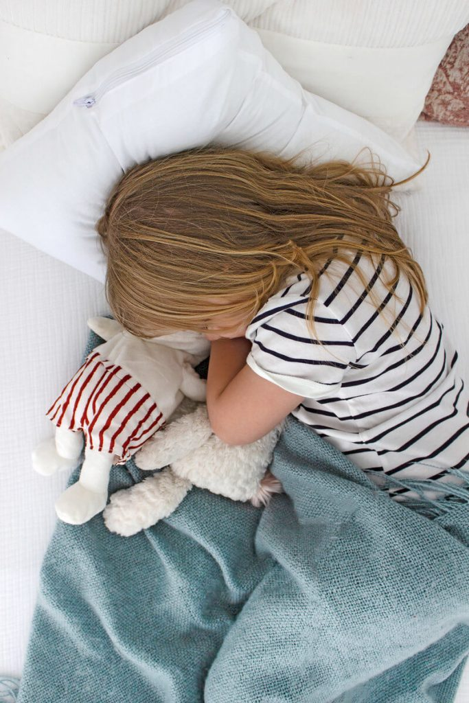 little girl sleeping in bed with blanket and stuffed animal