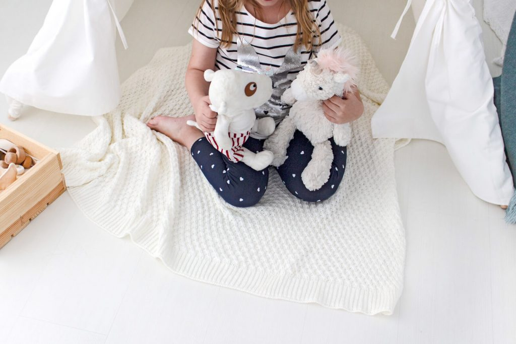little girl sitting on floor playing with stuffed animals