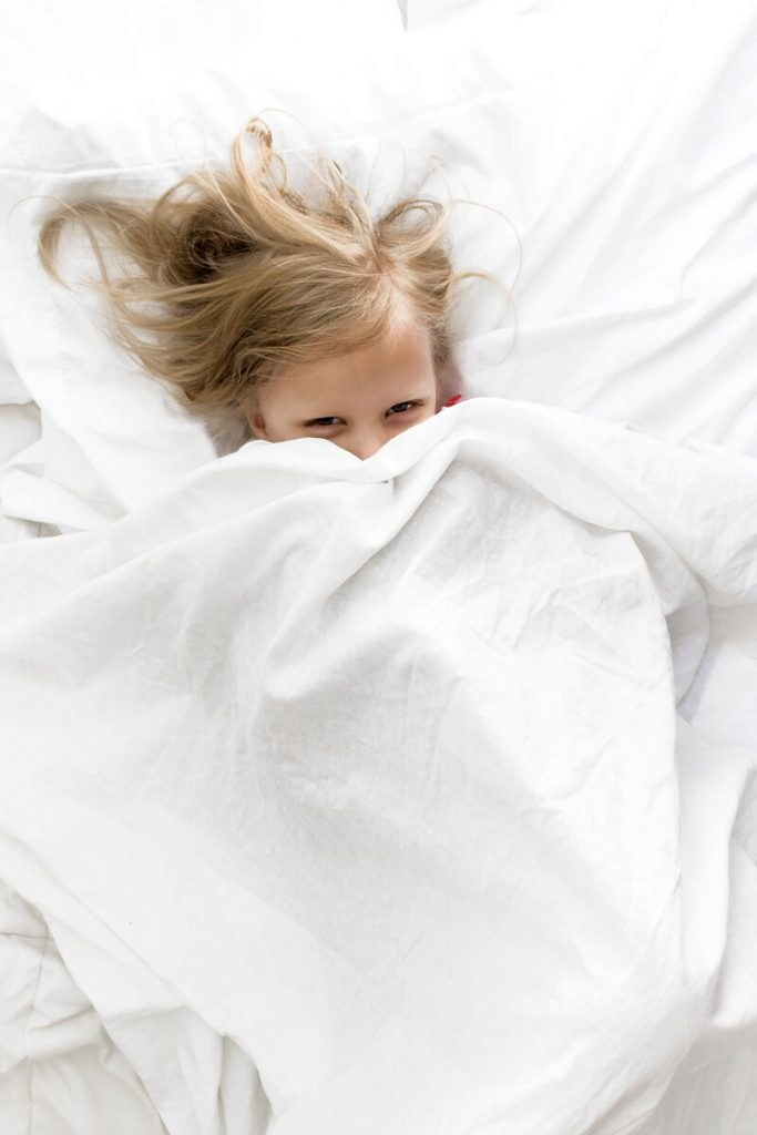 little girl laying under sheets in montessori floor bed