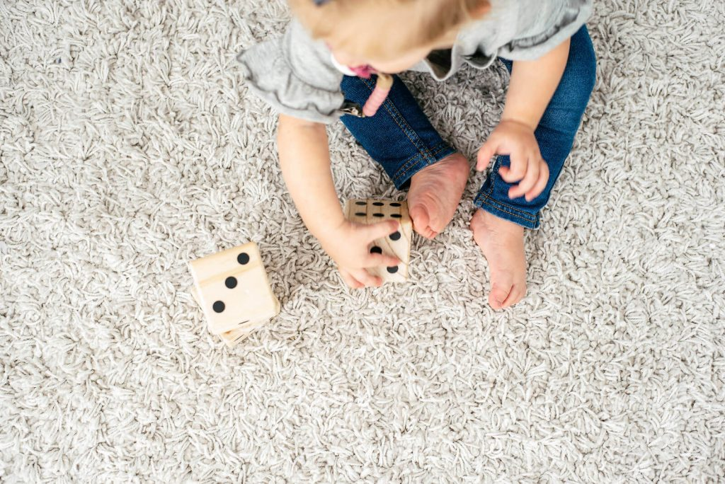 little toddler girl in jeans playing with wooden dice