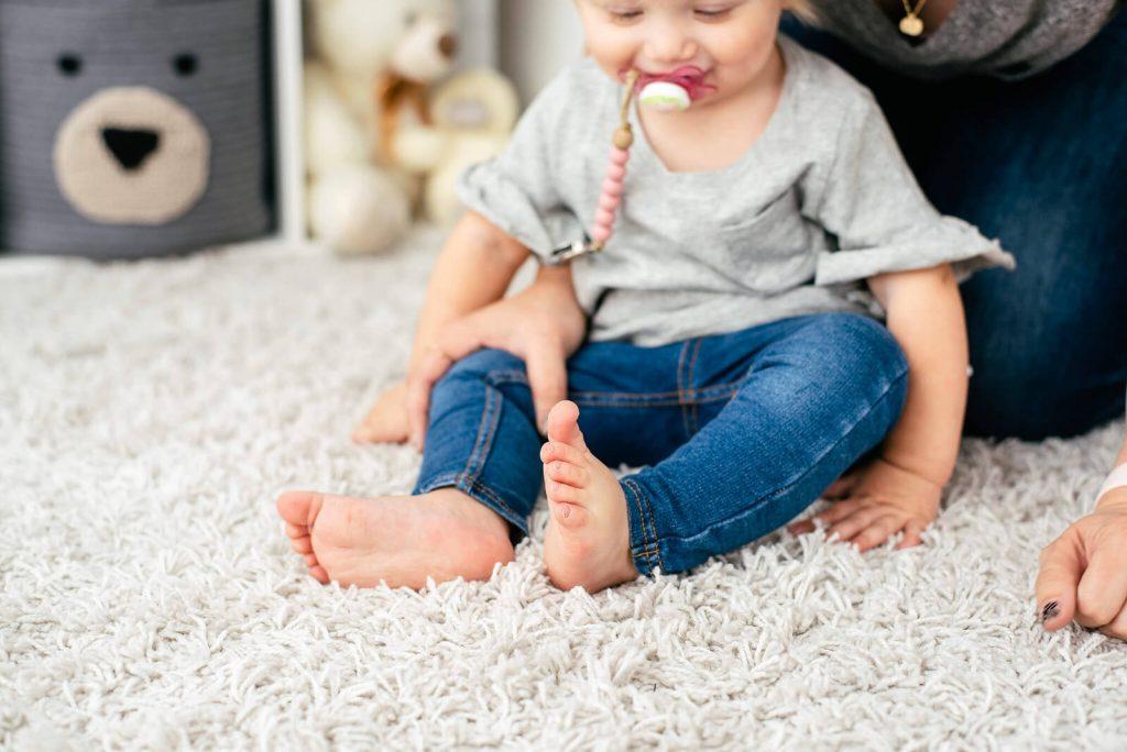 little toddler girl in jeans sitting on carpet floor