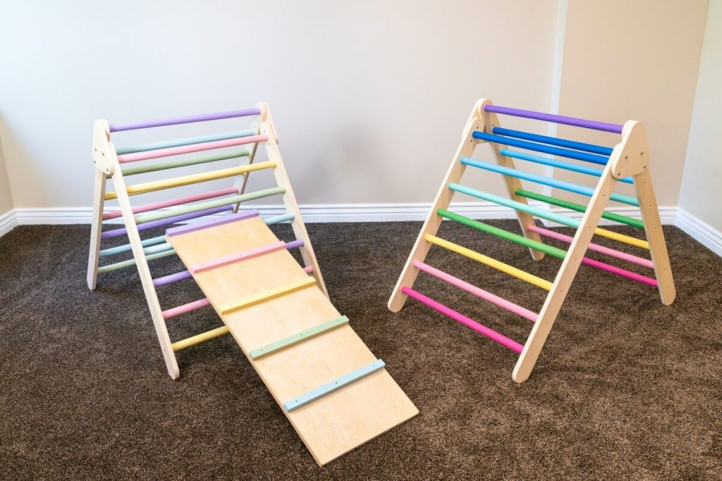 pikler triangle with rainbow painted rungs