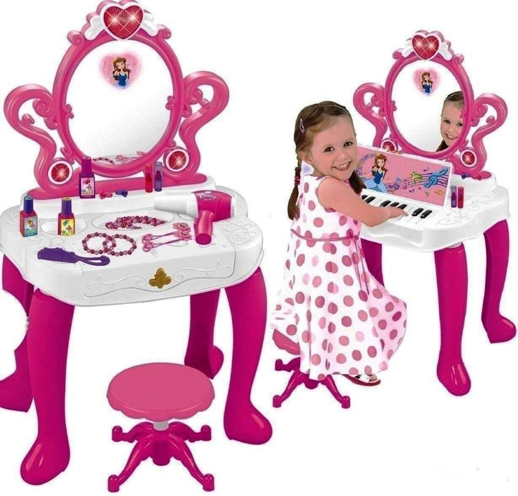 pink and white vanity with piano inside and little girl playning