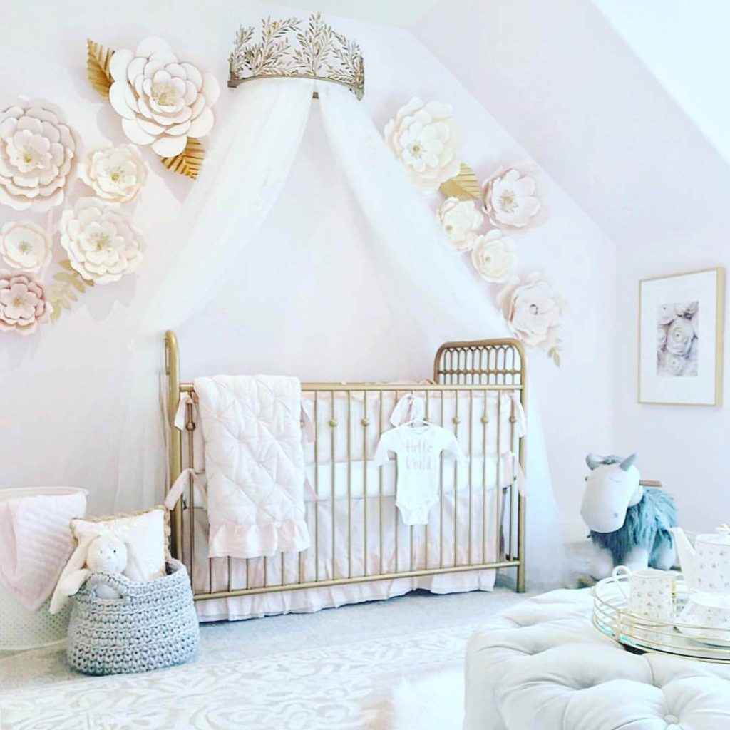 gold crib with princess crown on the wall with tulle hanging on either side and white flower wall decor