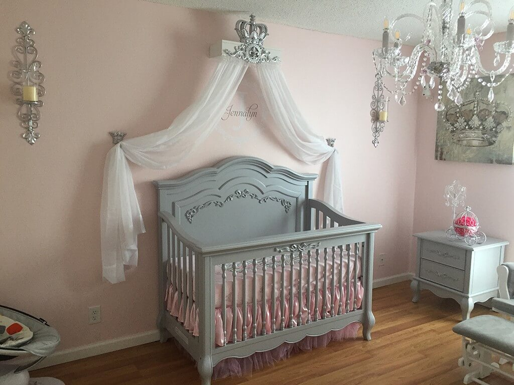 grey crib with pink walls and crown on the wall with tulle hanging down in princess nursery