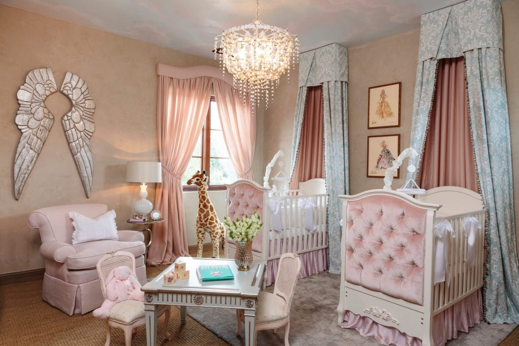 twin girl princess nursery with canopies on the wall with pink accents
