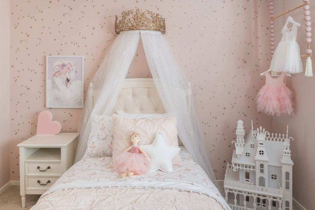 gold crown canopy on the wall on top of a twin bed with pink bedding