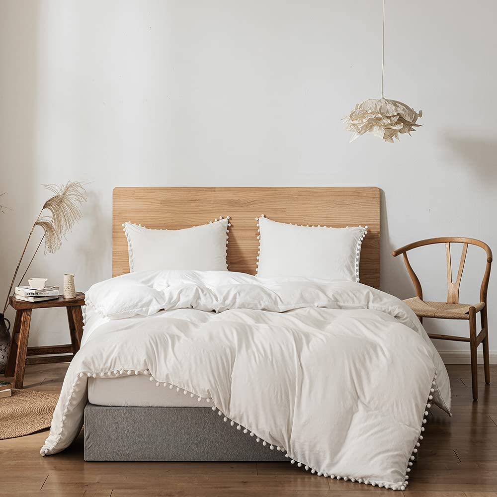 white bedding with wood bed and white wall