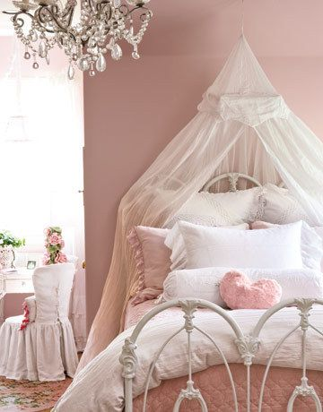 white tulle canopy on the wall on top of a twin bed with pink bedding