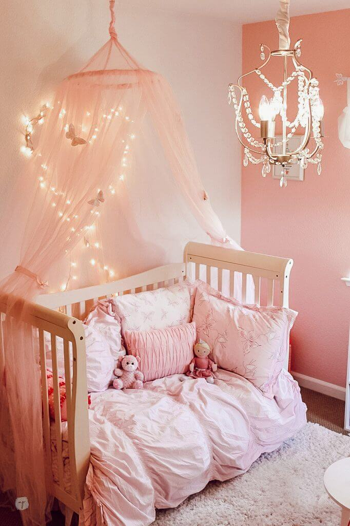pink princess room with pink bedding and pink tulle canopy with twinkly lights on the wall