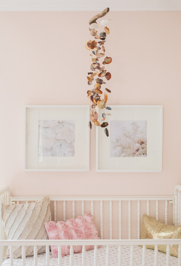 nursery with white crib and 2 white frames with wall painted Sherwin Williams Faint Coral