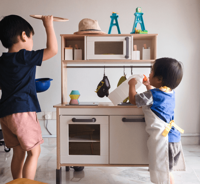 2 little boys playing with wooden play kitchen
