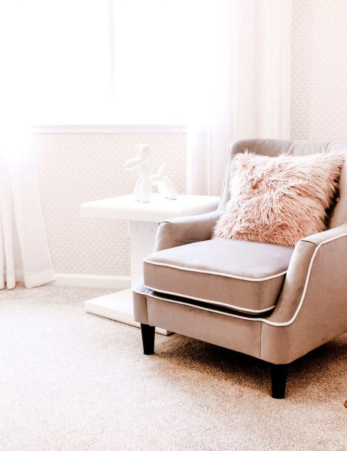 chair in nursery with pink bedding in white crib