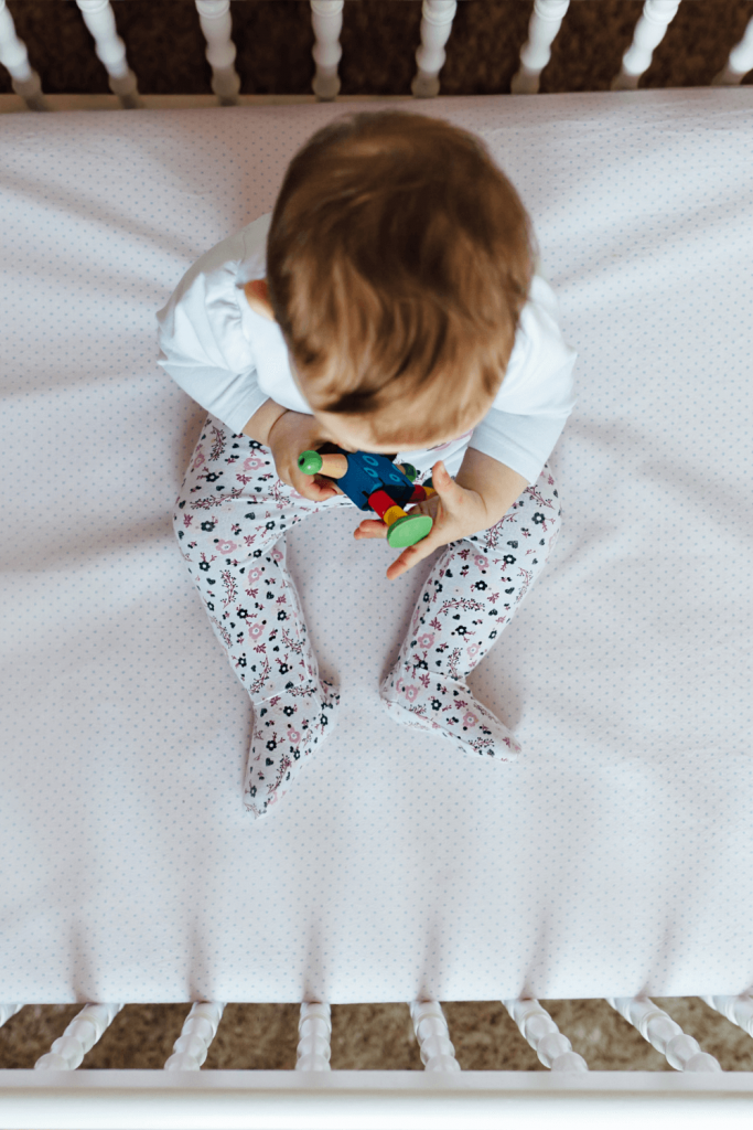 toddler sitting up in bed on white sheet