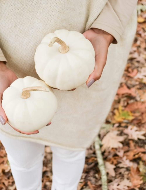 woman in white pants and cream top holding 2 white pumpkins