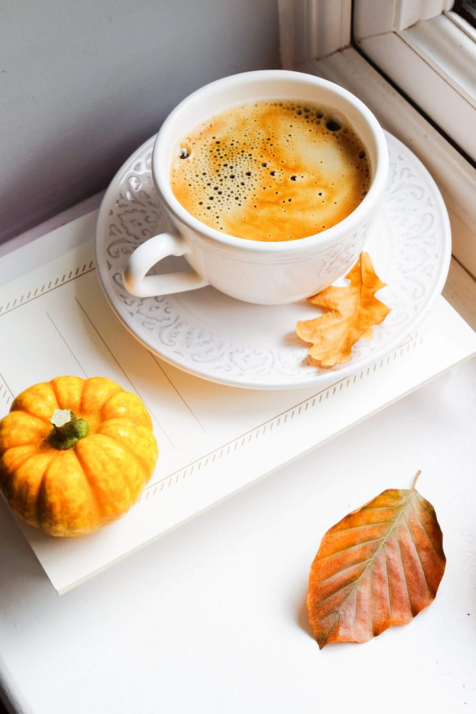 cup of pumpkin spice latte in white cup on a white tray with pumpkin and leaf on it