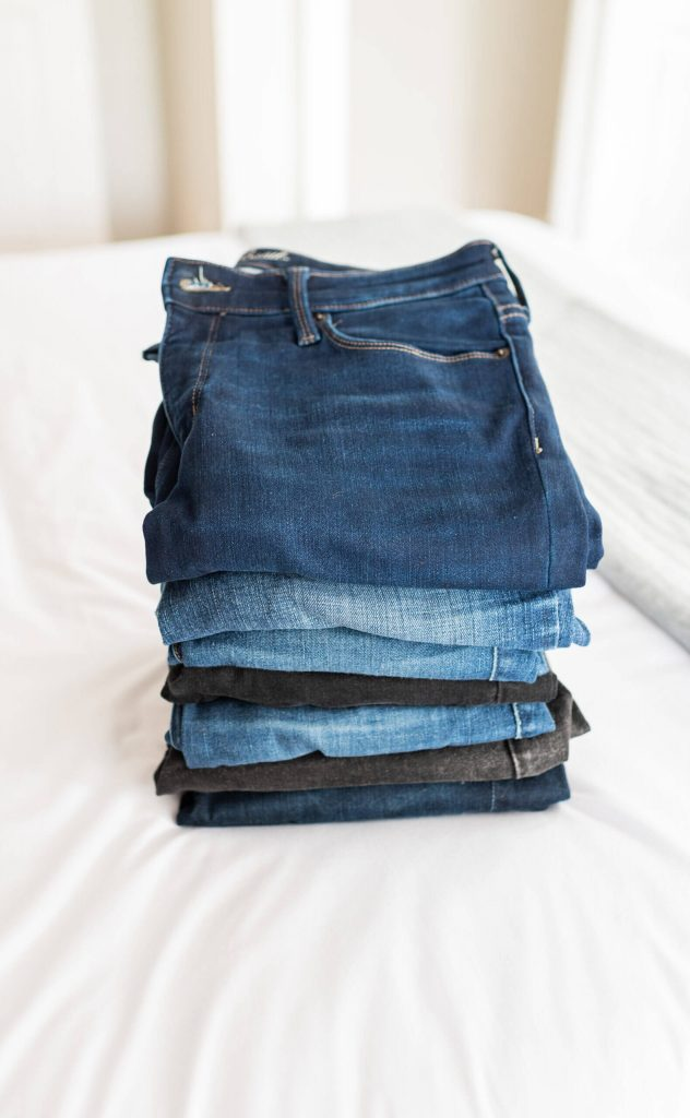 folded jeans on a white bed