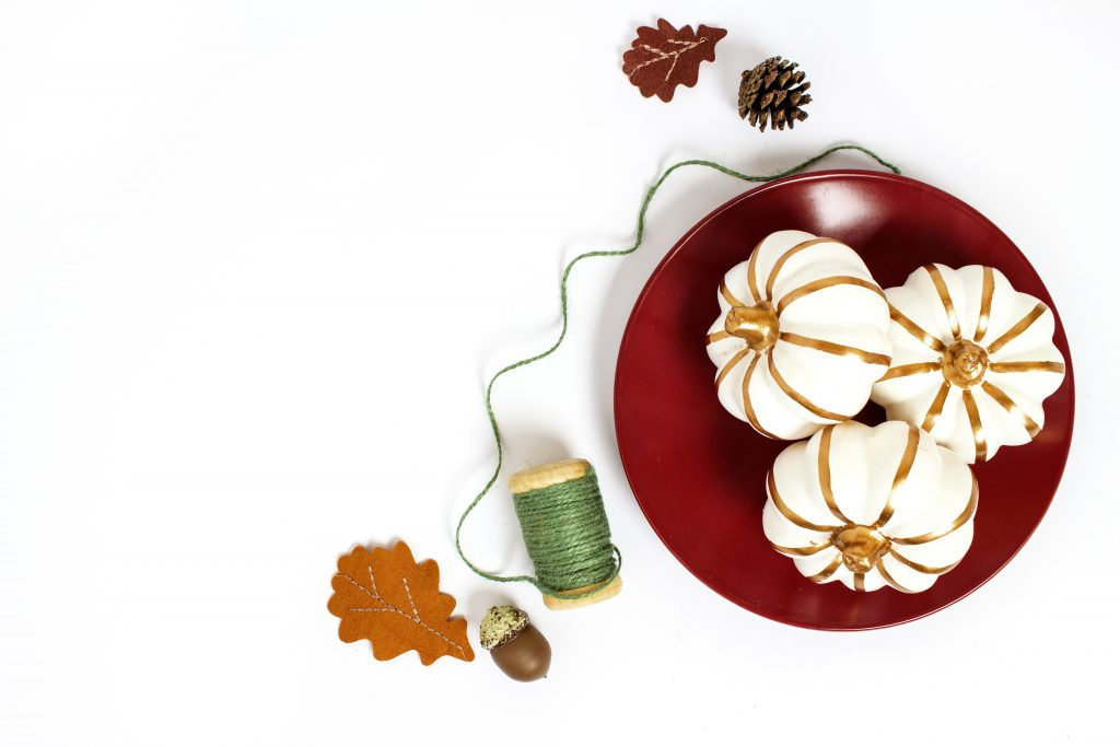 bowl of white pumpkins on white background with green thread and a leaf