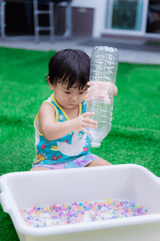 toddler holding water bottle over container of water beads