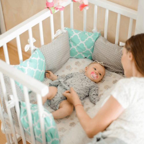 Mom looking at baby in a bedside mini crib