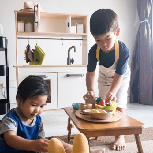 2 little boys playing with wooden play kitchen accessories